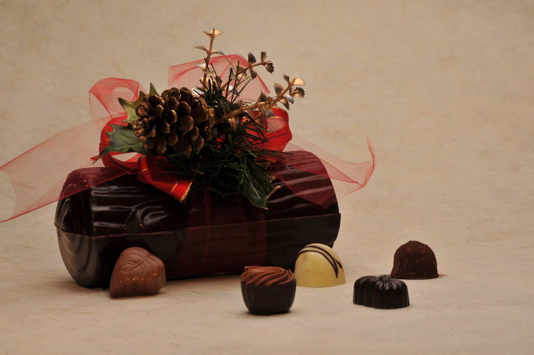 Chocolate Yule Log filled with 1/2 lb. of our Signature Chocolates, finished with a handmade holiday floral cluster.